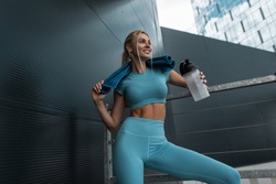 Pretty happy fitness model girl with slim body in fashion blue sportswear with shaker bottle and towel stands in the modern city