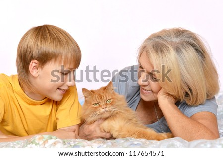 Pretty happy grandmother and grandson looking at pet cat