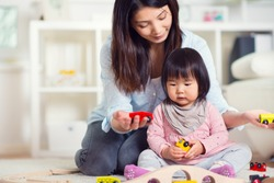 Pretty happy japanese mother play with her cute little toddler daughter at home