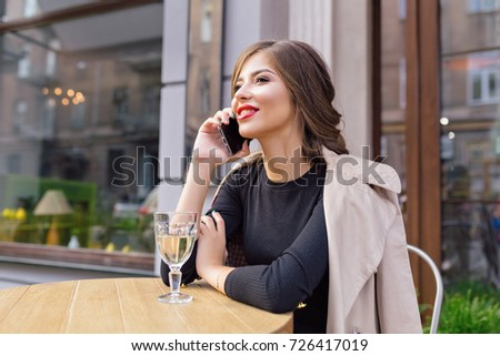 Pretty happy woman with stylish hairstyle and red lips is sitting on summer terrace with a glass of wine and talking on the phone. Outdoor portrait of attractive woman in restaurant with a phone