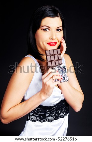 pretty happy young brunette woman eating dark chocolate
