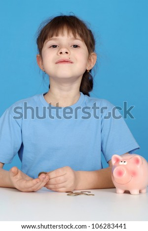 Pretty happy young girl sitting at a table with a piggy bank on a blue background