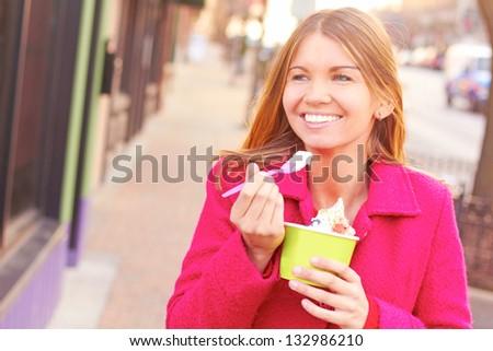 Pretty happy young pretty female eating frozen yogurt. Horizontal Shot.