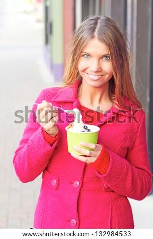 Pretty happy young pretty female eating frozen yogurt. Vertical Shot.