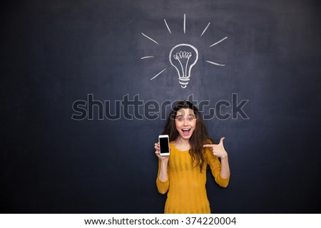 Pretty happy young woman holding and pointing on smartphone blank screen standing over chalkboard background