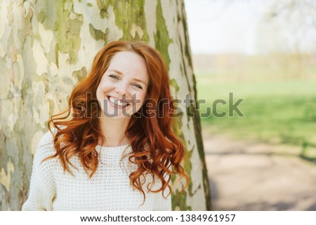 Pretty happy young woman outdoors in a park standing in front of a tree trunk grinning at the camera #1384961957