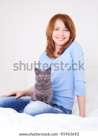 pretty happy young woman with her cat in bed at home