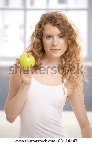Pretty, healthy girl after workout, holding apple in her hand.?