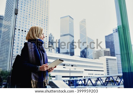 Pretty hipster girl dressed in spring clothes is holding portable touch pad and looking into the window on active life of New York Metropolitan city, while standing in skyscraper interior. Copy space