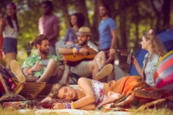 Pretty hipster relaxing on campsite at a music festival