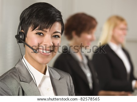 Pretty Hispanic Businesswoman with Colleagues Behind in an Office Setting.