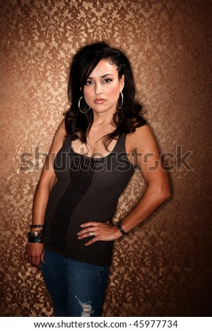 Pretty Hispanic Woman in Casual Clothes on Gold Wallpaper Background