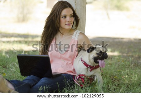 Pretty hispanic woman spending some time with her pug dog at the park