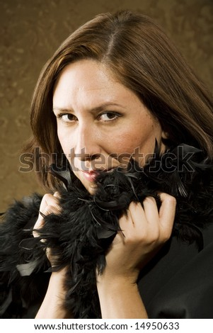 Pretty Hispanic Woman Wearing a Feather Boa in front of Gold Wallpaper