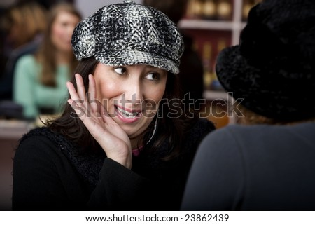 Pretty Hispanic woman with coffee sharing gossip