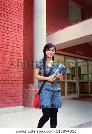 Pretty Indian / Asian college student standing outside the campus building with books in hand.