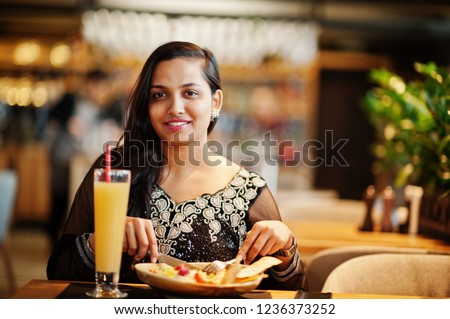 Pretty indian girl in black saree dress posed at restaurant, sitting at table with juice and salad. #1236373252