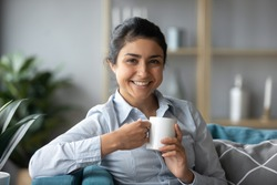 Pretty Indian girl sit on sofa with cup of fresh brewed tea relaxing alone in living room. Mixed-race housewife enjoy morning coffee at home feels happy, take break relish pause from housework concept