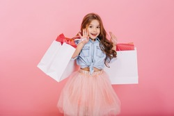 Pretty joyful young girl in tulle skirt, with long brunette hair walking with white packages on pink background. Lovely sweet moments of little princess, pretty friendly child having fun to camera