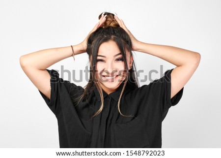 Pretty Kazakh Asian young woman in black with trendy bun of hair on head smiles and poses with stylish hairstyle isolated in white studio #1548792023