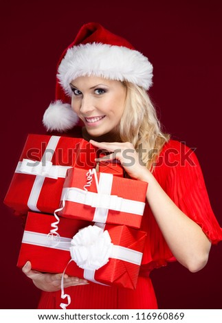 Pretty lady in Christmas cap holds a set of presents wrapped with red paper, isolated on purple