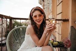 Pretty lady in white dress and sunglasses sits on terrace and holds white wine glass. Young woman with dark hair in red bandage on her head smiles