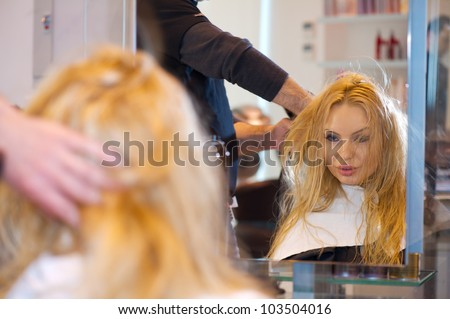 Pretty lady sitting while hairdresser dries her hair