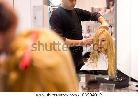 Pretty lady sitting while hairdresser fixes her hair