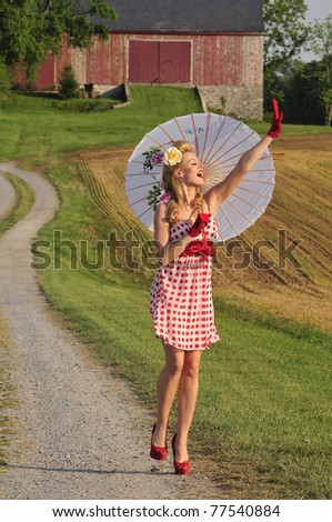 pretty lady walking in the country side with umbrella