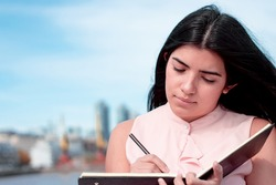 pretty latin girl, who is writing, taking notes in a black notebook with a black pen, in an urban industrial environment with the sky and buildings in the background. business and industrial concept.