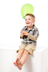 Pretty laughing boy with balloon sitting isolated on white background