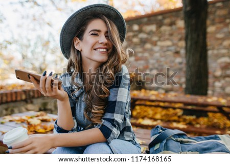 Pretty laughing girl with smartphone has a good time in autumn weekend. Outdoor portrait of lovable trendy lady with brown hair wears hat in october day.
