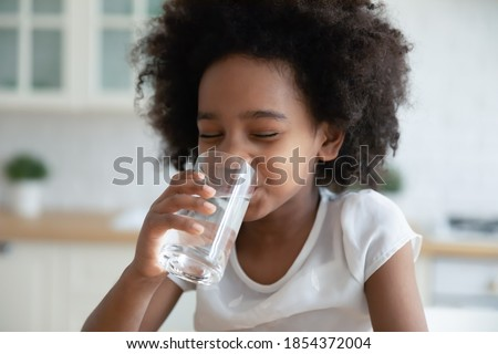 Pretty little African American girl drinking fresh water in kitchen close up, cute preschool child kid holding glass of pure mineral water, enjoying, healthy lifestyle and refreshment concept