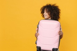 Pretty little african american kid girl 12-13 years old isolated on yellow background studio. Passenger traveling abroad on weekends getaway. Air flight journey concept. Hold suitcase, looking aside