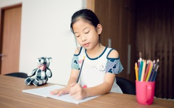 Pretty little asian girl enjoys learning and doing some homework in bedroom,Cute little asian girl writing her homework at the table.