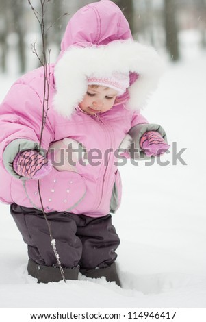 Pretty little baby girl playing in a snowy winter park