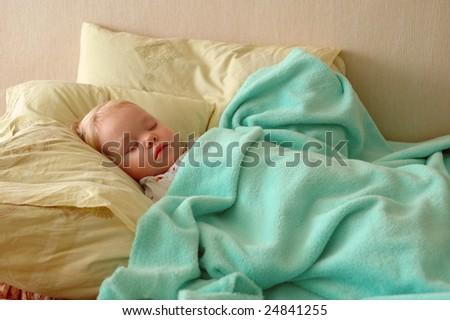 Pretty little blond girl sleep on two big pillows.