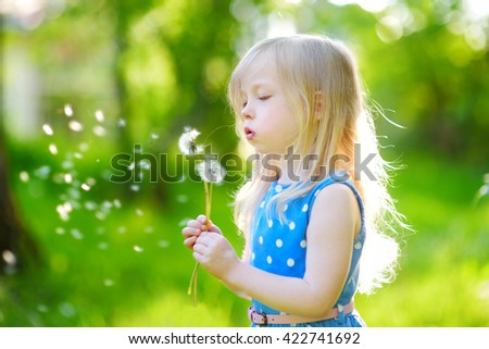 Pretty little blonde girl blowing off a dandelion on beautiful sunny summer day