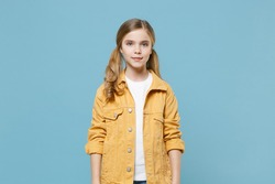 Pretty little blonde kid girl 12-13 years old in yellow jacket posing isolated on pastel blue wall background children studio portrait. Childhood lifestyle concept. Mock up copy space. Looking camera