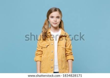 Pretty little blonde kid girl 12-13 years old in yellow jacket posing isolated on pastel blue wall background children studio portrait. Childhood lifestyle concept. Mock up copy space. Looking camera Stock photo ©