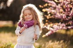 Pretty little child girl 4-5 year old with flowers over blooming nature background close up. Spring season. Childhood.