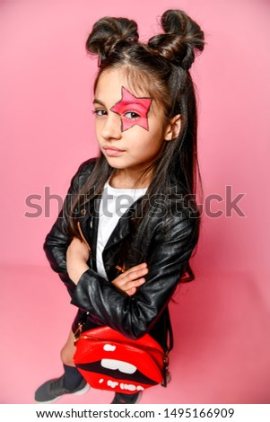 Pretty Little fashionable girl hipster punk - dressed in a leather jacket and skirt, black loaches and a white T-shirt, with a funny hairstyle and painted makeup star on her face. #1495166909