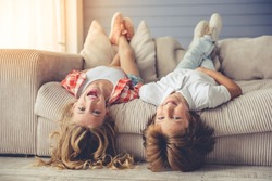 Pretty little girl and boy are lying on their backs on sofa, looking at camera and smiling while playing at home