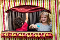 Pretty little girl and other children playing with hand puppets in small puppet theater
