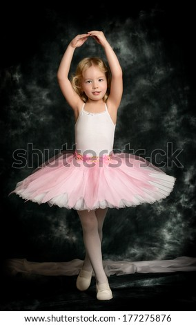 Pretty little girl ballerina in tutu posing over vintage background