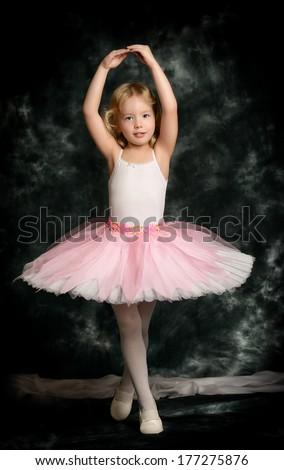Pretty little girl ballerina in tutu posing over vintage background