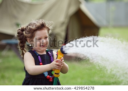 Pretty little girl dressed in a black dress denim jacket and red boots watering grass