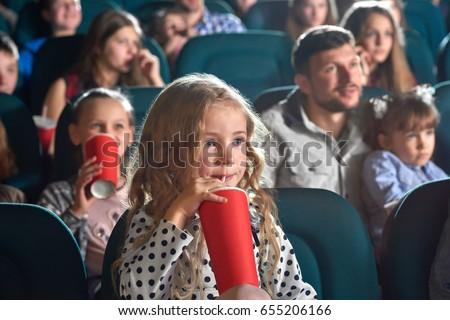 Pretty little girl drinking coke sitting at the movie theatre enjoying watching cartoon copyspace happiness positivity people leisure children child kids kid cuteness innocence entertainment activity. #655206166