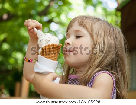 Pretty little girl eating an ice cream outdoors