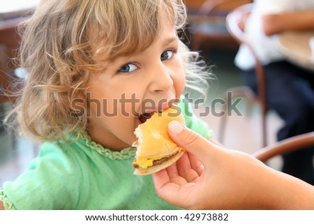 pretty little girl eats hamburger from mothers's hand - stock photo